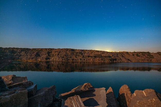 광산에서 열심히 일한 많은 석재 폐기물로 둘러싸인 매우 작은 아름다운 호수