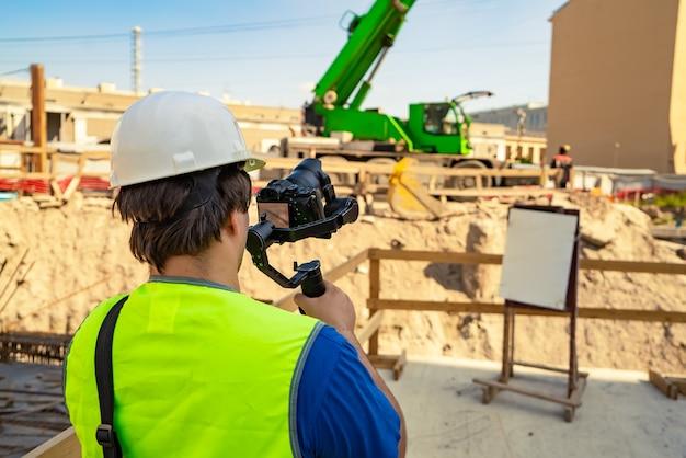 Видеооператор в защитном снаряжении с фотоаппаратом и стабилизатором в руках снимает рабочий процесс на стройплощадке.