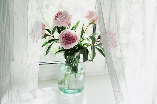 窓の花瓶に立っているピンクの牡丹の花束のビュー。コンセプトの背景、花、休日。