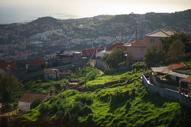 Вид на крыши фуншала и мадейры с кресельного подъемника, поднимающегося на холм за городом.