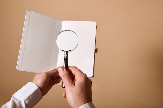 Вид изображения белого чистого листа с лупой или увеличительным стеклом в женских руках на бежевой стене с копией пространства