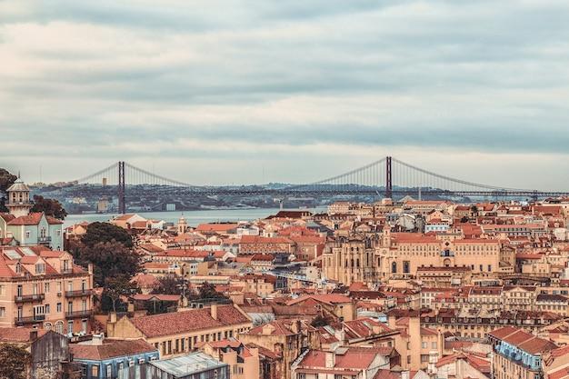Вид на центр города алфама и мост 25 апреля, лиссабон, португалия.