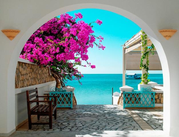 Вид на синее море туниса через белую арку с розовыми цветущими цветами на переднем плане вдали дом на воде