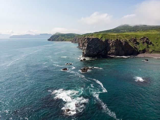 澄んだ青い海の側からのカムチャツカの岩の多い海岸の眺め