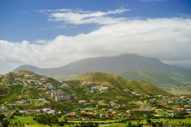 Вид на остров сент-китс с жилым районом и пышными зелеными холмами на заднем плане.