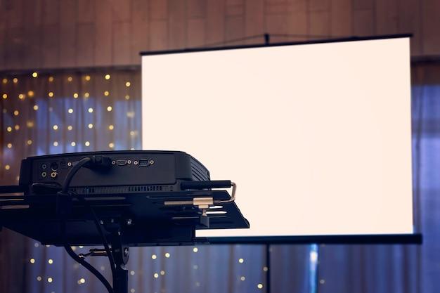 Вид на проекционное оборудование на фоне украшенных оконных занавесок банкетного зала. оборудование для видео- и аудиопроекции на праздничном мероприятии. размещение шоу на банкете.