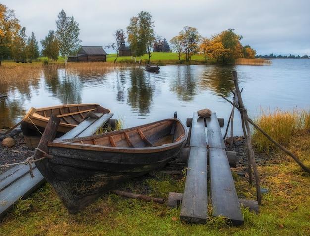 Деревенская рыбацкая лодка из досок в музее-заповеднике кижи на севере россии на онежском озере с пристанями и пристанью в пору золотой осени.
