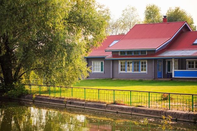 晴れた日の森の中の川沿いの村の家は、きれいな自然の中で暮らすのに良い場所です...