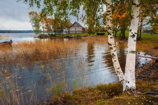 Деревенский дом из бревен в музее-заповеднике кижи на севере россии на онежском озере с пристанью и пристанью в пору золотой осени.