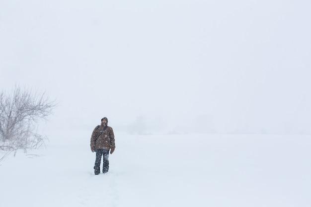 Деревенский мужчина гуляет зимой в поле. снежная метель.