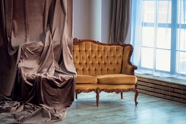 미니멀 한 스타일의 객실 내부에 벨벳 커튼으로 덮인 빈티지 브라운 소파. 파노라마 창
