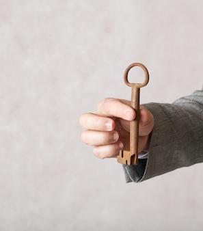 Старинный ключ в руке мужчины в классическом костюме. крупный план.