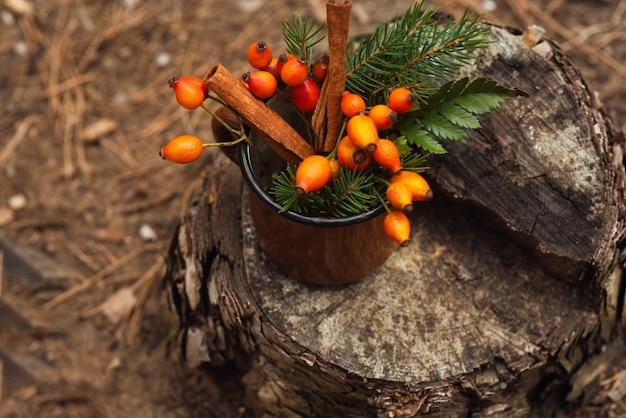 ローズヒップ、緑の葉、トウヒの枝、シナモンが入ったヴィンテージの古いマグカップが森の切り株に立っています。新年とクリスマスの背景。冬の雰囲気。ベリー入りのヘルシーなハーブティー