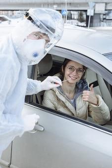 Ppe化学防護服を着用しているウイルス学者または医師は、車の中で女性ドライバーから綿棒を使用してpcrテストのサンプルを採取します。