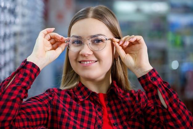 視覚障害のある少女が眼鏡を選びます。彼女はシャツと美しい笑顔を着ています。
