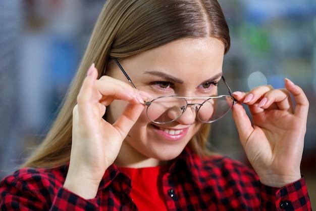 Слабовидящая девушка выбирает очки. на ней рубашка и красивая улыбка.