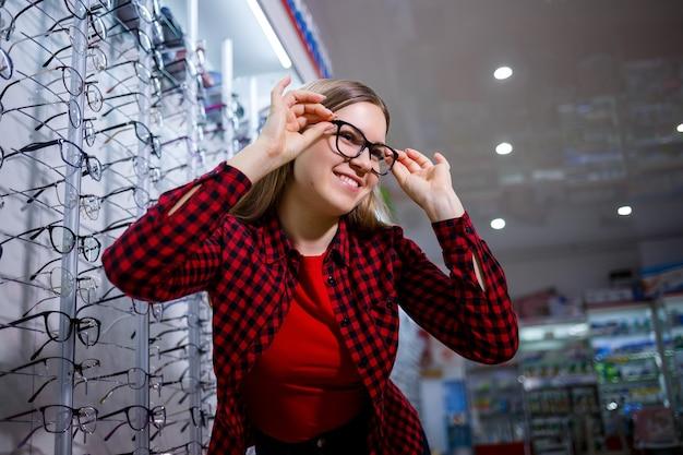시각 장애인 소녀가 안경을 선택합니다. 그녀는 셔츠를 입고 아름다운 미소를 짓고 있습니다.