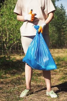 자원 봉사자가 숲에서 플라스틱 병을 수집합니다. 소녀는 손에 쓰레기 봉투를 들고 손으로 제스처를 보여줍니다. 환경, 지구를 보호하기 위한 개념 호출.