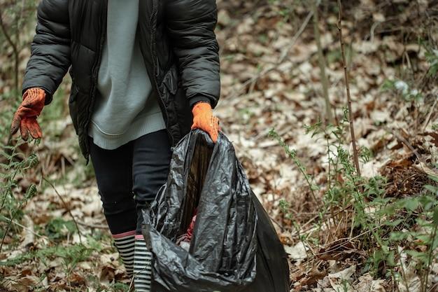 Девушка-волонтер с мешком для мусора убирает мусор в лесу.