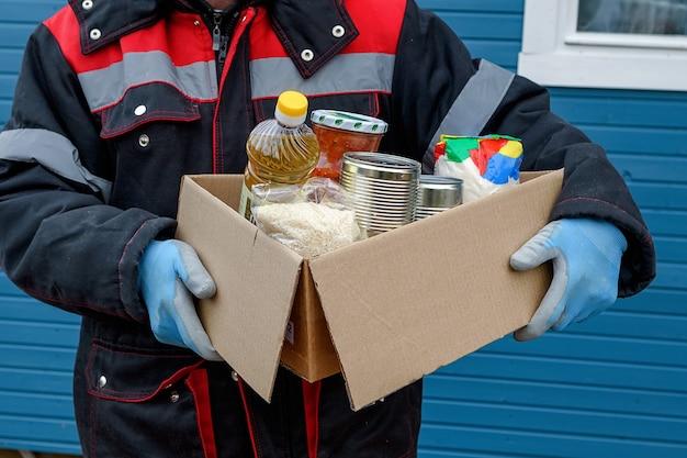 冬のジャケットを着たボランティアが、ドライシリアル、缶詰、バターなどの製品が入った段ボール箱を持っています。パンデミックの際に助けてください。食糧の寄付または食糧配達の概念。