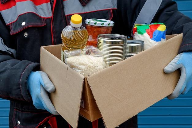 冬のジャケットを着たボランティアが、ドライシリアル、缶詰、バターなどの製品が入った段ボール箱を持っています。