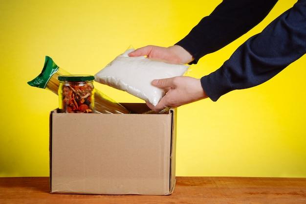 Волонтер кладет еду в ящик для пожертвований. помощь бедным людям в условиях самоизоляции