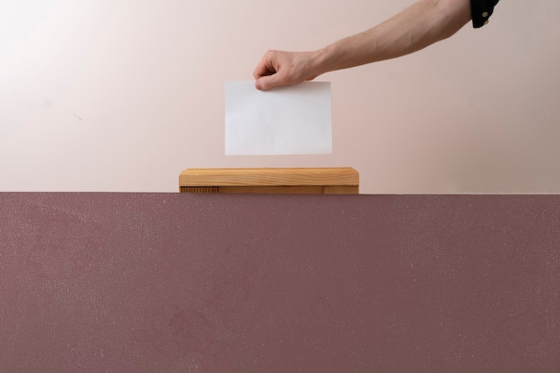有権者の手が骨壷に紙を置き、民主主義の選挙