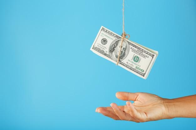 Валюшка долларов на строке над человеческой ладонью на сини.
