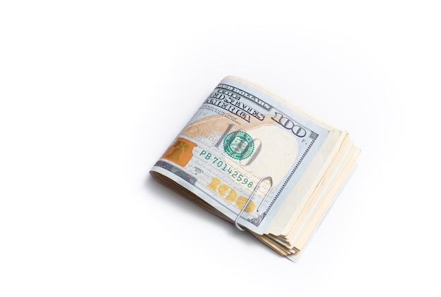 Пачка сложенных долларовых купюр, изолированных на белом на фото крупным планом