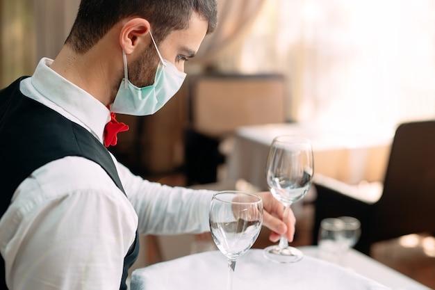 医療用防護マスクのウェイターがレストランのテーブルで働いています。