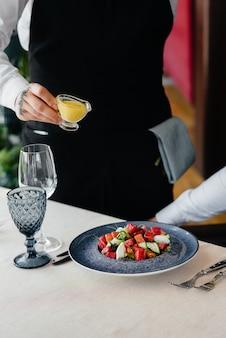 웨이터는 클로즈업에서 야채와 참치의 신선한 샐러드 위에 소스를 붓습니다. 건강한 음식.