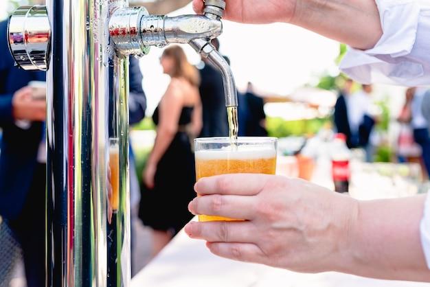 ウェイターは、チラーコイルからグラスを満たしてビールを出します。