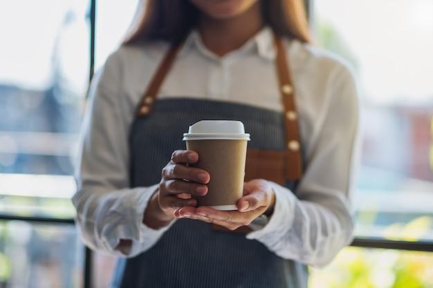 カフェでホットコーヒーの紙コップを保持し、提供するウェイトレス