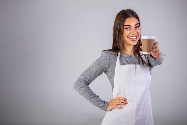Официантка держит и подает бумажный стаканчик горячего кофе на сером
