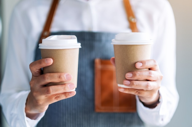カフェで2杯のホットコーヒーを持って提供するウェイトレス