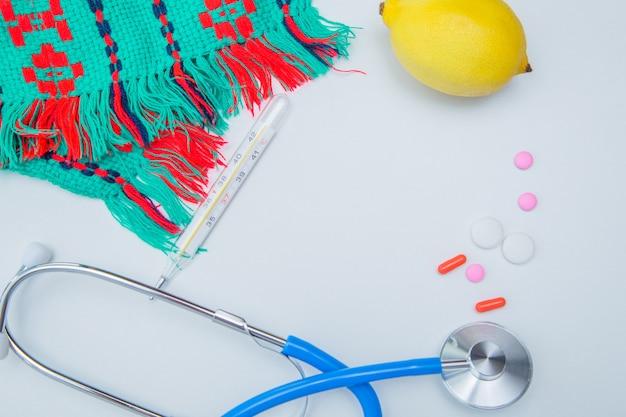 暖かい冬のスカーフ、温度計、レモン、聴診器、カプセル付きの錠剤が白い背景に横たわっています...