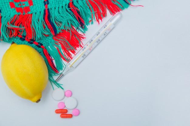 暖かい冬のスカーフ温度計レモンとカプセル付きの丸薬は、白い背景の側面にあります...