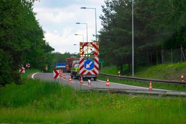 道路の警告標識が前方に走っています。道路標識。道路の修理。