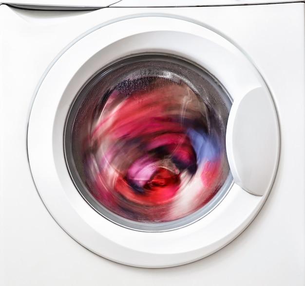 Стиральная машина стирает цветное белье крупным планом. бытовая техника