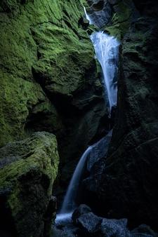 Водопад у замшелых скал в начале лета.