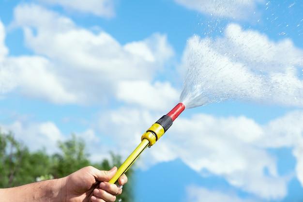 Мужчина держит поливочный шланг, из которого льется вода на фоне голубого неба.