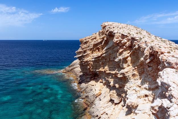 Волна, застывшая в камне в изумрудном море на пляже на ибице, испания