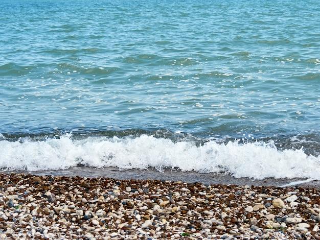 По галечному берегу катится волна