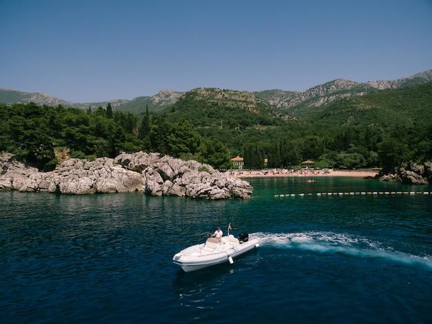 裕福な男が豪華な別荘とビーチを背景にスポーツボートを運転します