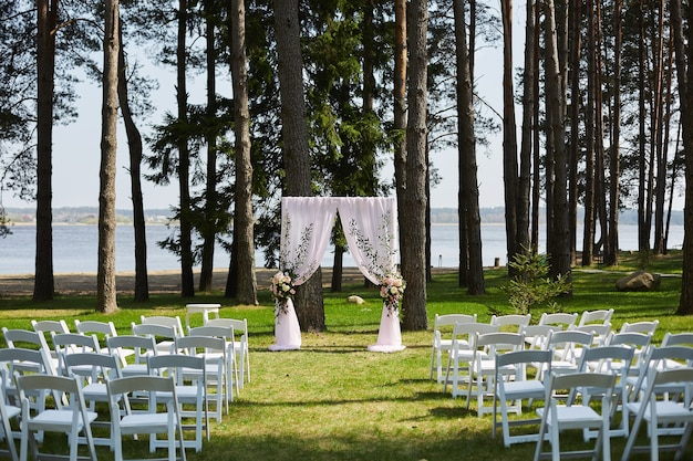 Свадебная арка, украшенная живыми цветами и пустыми стульями, подготовленная для свадебной церемонии на открытом воздухе в лесу у берега озера