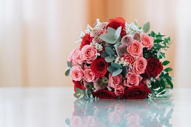 Свадебный букет из красных и розовых роз лежит на стеклянной поверхности.