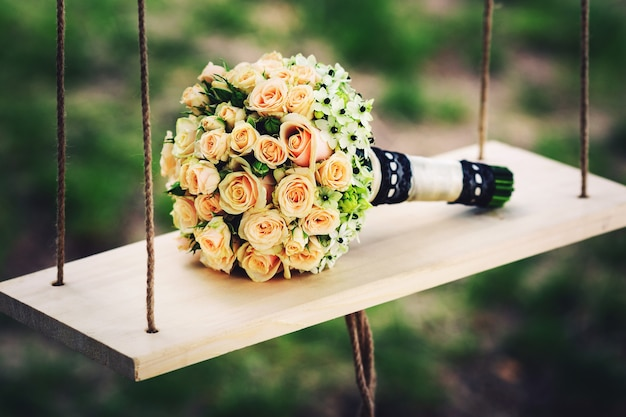 バラのウェディングブーケは、自然の中で木製のブランコに横たわっています