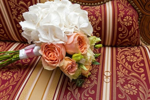 장미 꽃다발이 바로크 소파에 놓여 있습니다. 장미 꽃다발, 결혼식 꽃입니다.