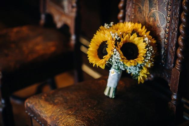 ひまわりのウェディングブーケは、アンティークの椅子の上にあります。結婚式の装飾
