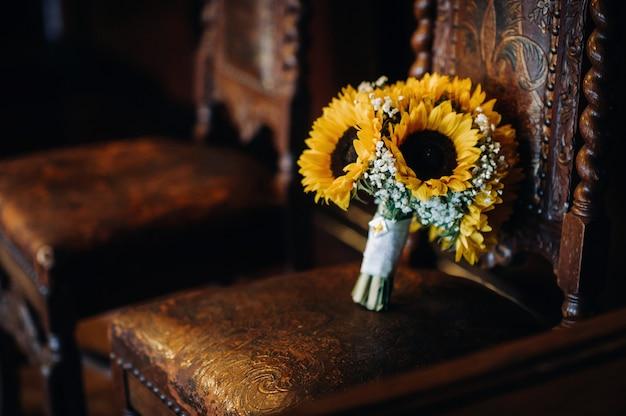 ひまわりのウェディングブーケはアンティークの椅子に横たわっています結婚式の装飾